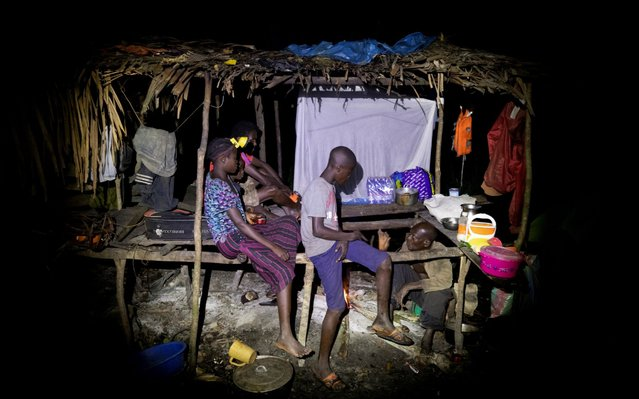The hunters and their children rest at night after paddling for eight hours to get to their campsite in the forest near Mbandaka, Democratic Republic of the Congo, April 2, 2019. (Photo by Thomas Nicolon/Reuters)