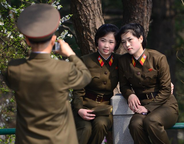 Two female soldiers have their picture taken by an army colleague at Mangyongdae. (Photo by Gavin John/Mediadrumworld.com)