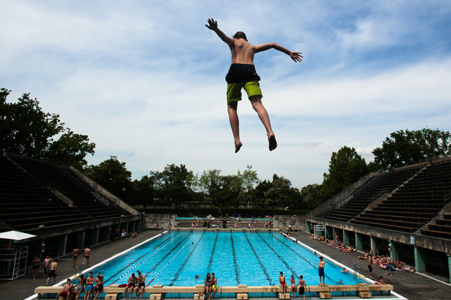A boy jumps into the water at the Olympic open air public pool in Berlin, Germany, Wednesday, May 21, 2014. An early summer day hits the German capital with temperatures up to about 30 degrees Celsius (86 Fahrenheit). (Photo by Markus Schreiber/AP Photo)