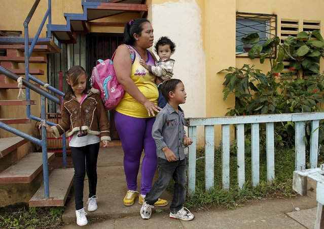 Hazel Castillo leaves her home with her three children to an aerobics class in Los Guidos de Desamparados July 23, 2015. (Photo by Juan Carlos Ulate/Reuters)