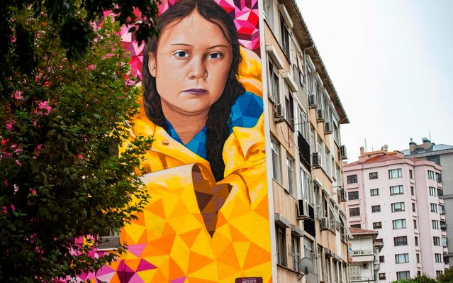 """A mural with the portrait of Swedish climate activist Greta Thunberg, painted by Portuguese artists Mr. Dheo and Pariz One, is seen on a building in the Kadikoy district in Istanbul on September 20, 2019. Swedish teen activist Greta Thunberg, who inspired the Friday's climate protests around the world, in an interview with AFP has expressed hope that climate strikes will be a """"social tipping point"""". (Photo by Yasin Akgul/AFP Photo)"""