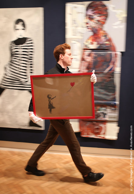 Employee George Foren holds Banksy's 'Girl and Balloon', which was painted on an Ikea frame, at Bonhams auctioneers