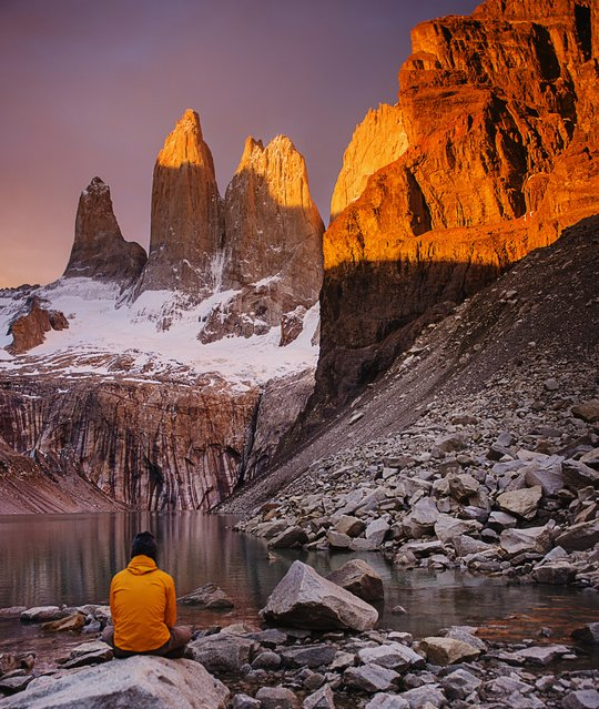 """""""Torres Del Paine"""". Lone hiker in an orange jacket watching the sunrise in front of Mirador Torres in Torres Del Paine National Park in Patagonia. Photo location: Torres Del Paine, Chile, Patagonia, South America. (Photo and caption by Michael Marquand/National Geographic Photo Contest)"""