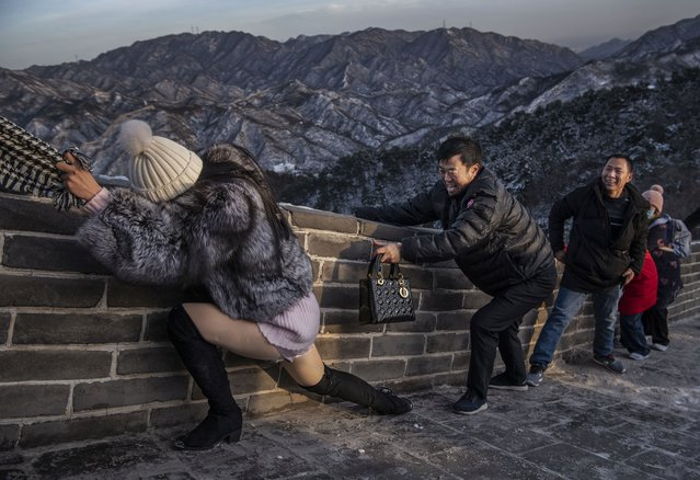 A Chinese tourist uses the scarf of a friend as she is helped while she and others struggle to climb in the wind on an icy section of the Great Wall at Badaling, on a cold day after a snowfall on November 30, 2019 in Beijing, China. (Photo by Kevin Frayer/Getty Images)