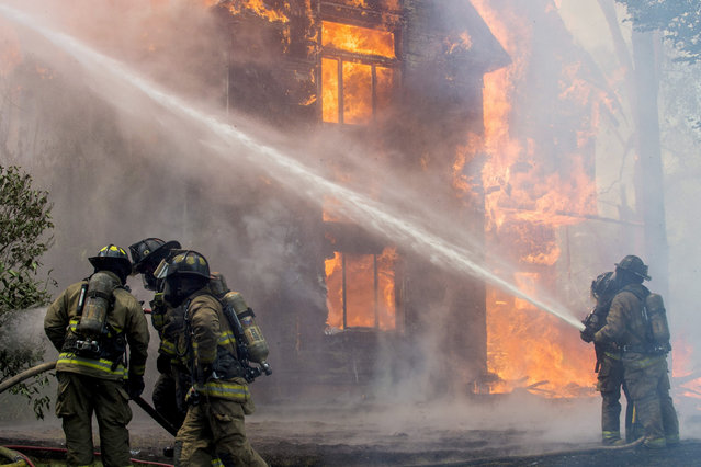 Flint firefighters cool the side of a neighboring home, which eventually caught on fire, as they battle a raging blaze that spans two homes on Wednesday, July 22, 2015 just north of downtown in Flint, Mich. (Photo by Jake May/The Flint Journal-MLive.com via AP Photo)