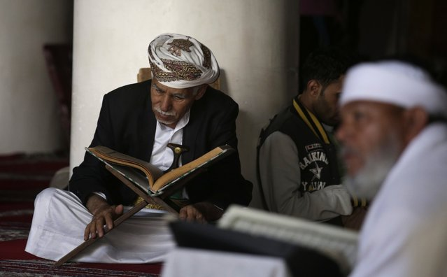 An elderly man, center, reads verses of the Quran, Islam's holy book, on the first day of the fasting month of Ramadan in the Grand Mosque in the old city of Sanaa, Yemen, Monday, June 6, 2016. (Photo by Hani Mohammed/AP Photo)