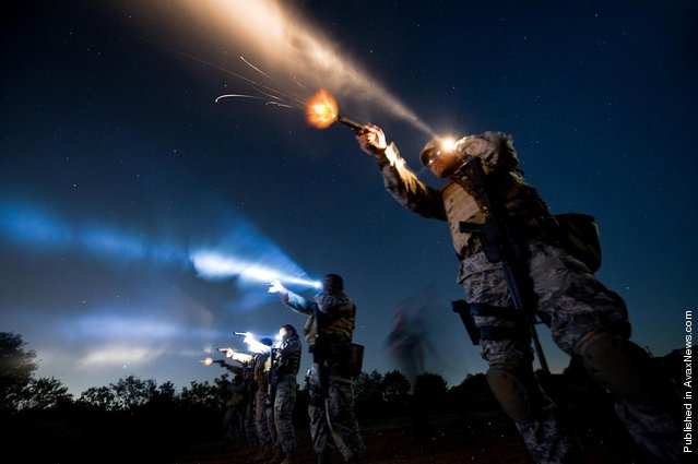 Tech. Sgt. Milo Hinson, 3rd Combat Camera Squadron, uses a flashlight while shooting a Berretta 9mm during the night-fire portion of Advance Weapons, Tactics and Techniques training in San Antonio. During night-fire training, airmen learn how to tactically illuminate targets with flashlights and practice using night vision goggles