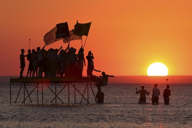 Visitors to the Befooz electronic music festival, which was banned by the Crimean prosecutor's office, relax at the sea during sunset in the village of Popovka, Crimea, August 1, 2015. (Photo by Pavel Rebrov/Reuters)