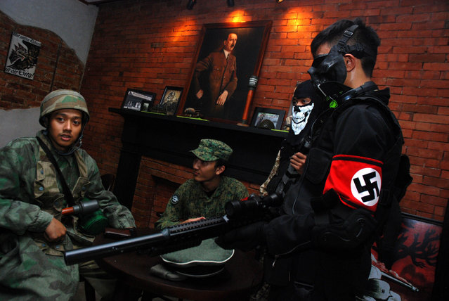 Indonesian customers come in World War II motif military uniforms, one bearing a Nazi's swastika insignia while a portrait of Adolf Hitler hangs in the background, at the reopened SoldatenKaffee in Bandung city, western Java island on June 21, 2014. The Nazi-theme cafe in Indonesia that sparked international outrage and closed shop, has reopened with its walls still bearing swastikas and a large painting of Adolf Hitler. (Photo by Timur Matahari/AFP Photo)