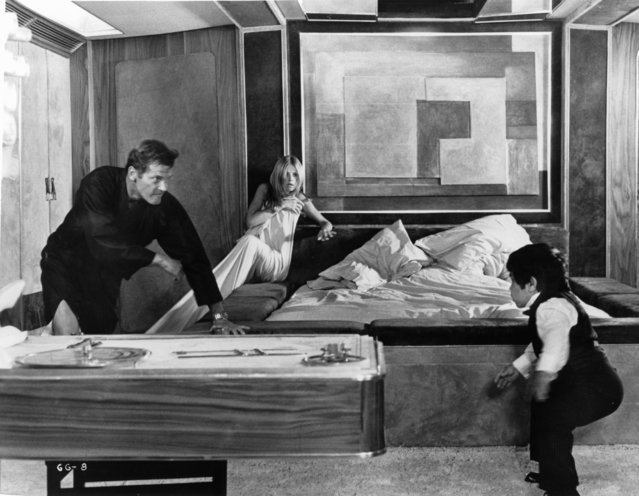 """Roger Moore chasing Hervé Villechaize while Britt Ekland huddles against the wall with a sheet wrapped around her in a scene from the film """"The Man With The Golden Gun"""", 1974. (Photo by United Artists/Getty Images)"""