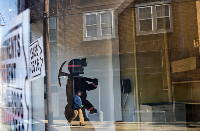 In this October 17, 2014 photo, a mural of a coal miner stands in an empty storefront as signs advertising vacant apartments and stores hang in the windows along the main business street in Cumberland, Ky. (Photo by David Goldman/AP Photo)