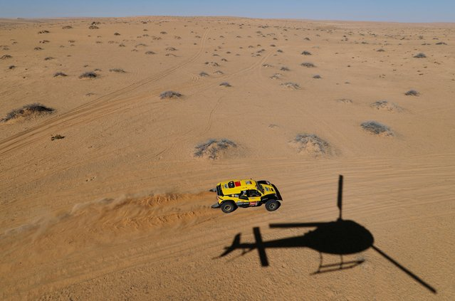 Geely Auto Shell Lubricant Team's Wei Han and Min Liao are pictured as a helicopter flies overhead during Stage 5 of the Dakar Rally in Saudi Arabia on January 9, 2020. (Photo by Hamad I Mohammed/Reuters)