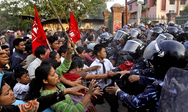 Nepalese police scuffle with illegal squatters residing on the banks of the Bagmati River in Katmandu on May 8, 2012