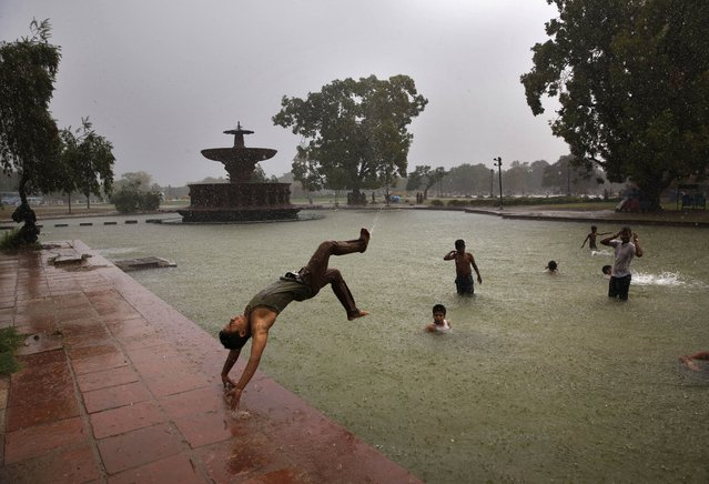 A boy somersaults into a water body as it rains in New Delhi, India, Wednesday, July 2, 2014. According to the weather office, the monsoon rains are expected to arrive at the national capital in a couple of days. (Photo by Manish Swarup/AP Photo)