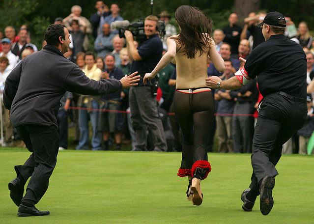 Marshalls try to get their hands on a streaker as golfers Michael Campbell of New Zealand and Paul McGinley of Ireland play the World Match Play final at Wentworth golf club some 20 miles west of London, 18 September 2005. Campbell won the title at the 17th hole. (Photo by Odd Andersen/AFP Photo)