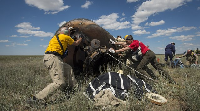 A handout phptopgraph made avaiable by NASA showing Russian support personnel roll the Soyuz TMA-19M spacecraft after it landed with with with Expedition 47 crew members Tim Kopra of NASA, Tim Peake of the European Space Agency, and Yuri Malenchenko of Roscosmos near the town of Zhezkazgan, Kazakhstan 18 June 2016. Kopra, Peake, and Malenchenko are returning after six months in space where they served as members of the Expedition 46 and 47 crews onboard the International Space Station. (Photo by Bill Ingalls/EPA/NASA)