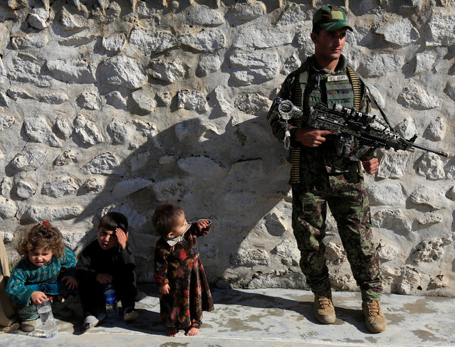 A member of the Afghan security forces watches next to family members of ISIS militants who surrendered to the Afghan government in Achin district of Nangarhar province, Afghanistan on November 17, 2019. (Photo by Reuters/Parwiz)