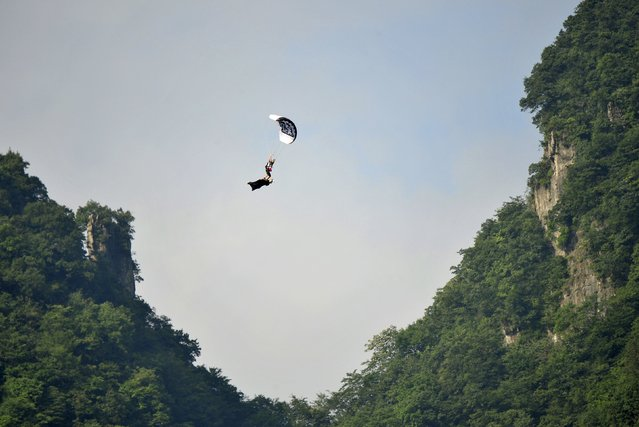 Norway's paraglider Bjoern Magne Bakke Bryn (top) lands on his compatriot wingsuit flyer Espen Fadnes as they travel past the Tianmen Mountain during a challenge, in Zhangjiajie, Hunan province, China, August 11, 2015. The two extreme sports enthusiasts successfully completed the challenge on Tuesday after taking off from different locations and joining together in mid-air, local media reported. (Photo by Reuters/China Daily)