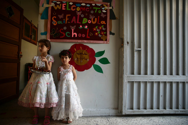 Girls stand welcoming visitors with dates at the entrance of their school in the town of Douma, eastern Ghouta in Damascus, Syria May 25, 2016. (Photo by Bassam Khabieh/Reuters)