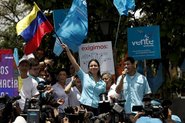 Venezuela's opposition leader Maria Corina Machado (C) waves a national flag during a meeting with supporters, after trying to register her candidacy for the upcoming parliamentary elections at an office of National Electoral Council (CNE), in Los Teques, Venezuela August 3, 2015. (Photo by Carlos Garcia Rawlins/Reuters)
