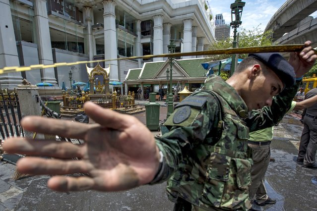 A member of military personnel stops the media from taking pictures at the Erawan shrine, the site of a deadly blast, in central Bangkok, Thailand, August 18, 2015. (Photo by Athit Perawongmetha/Reuters)