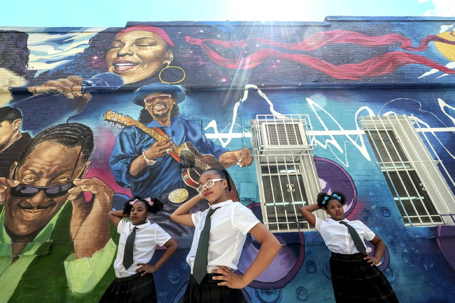 Mariyiah Thompson, 9, Amiyah Wright, 10, and Jaylah Carter, 11, with Visions Perfoming Arts Company, practice prior to a ribbon cutting celebration for a new mural honoring famous personalities on a wall at Ben's Chili Bowl in Washington, DC on June 21, 2017. The mural was created by Aniekan Udofia using subjects chosen by an online community. Donnie Simpson, Chuck Brown and Roberta Flack are among the celebrities depicted. (Photo by Bonnie Jo Mount/The Washington Post)