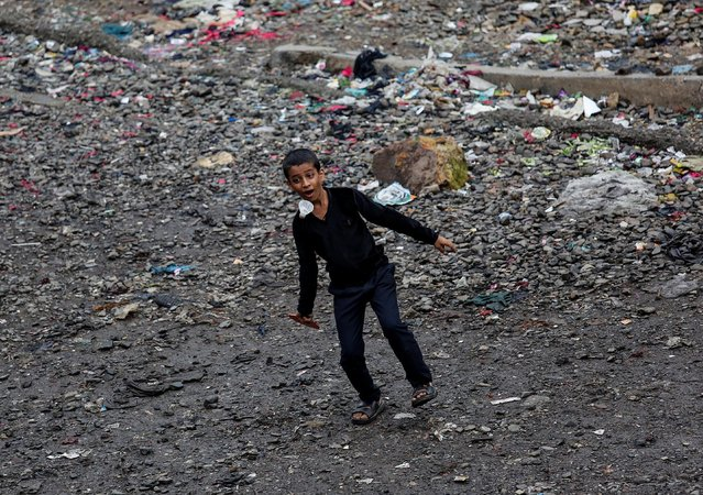 A boy tries to hit a shuttlecock with a wooden bat at a slum in Mumbai, India, June 29, 2016. (Photo by Danish Siddiqui/Reuters)