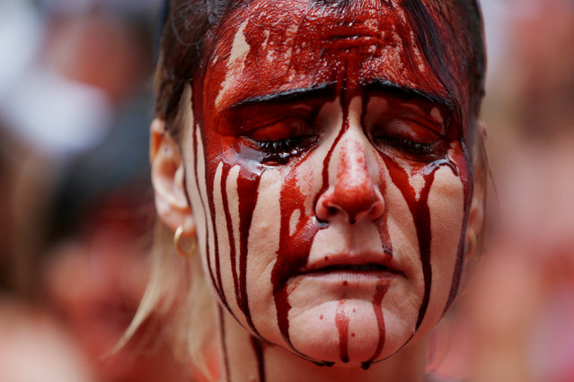 An animal rights protester covered in fake blood reacts during a demonstration for the abolition of bull runs and bullfights a day before the start of the famous running of the bulls San Fermin festival in Pamplona, northern Spain, July 5, 2016. (Photo by Susana Vera/Reuters)