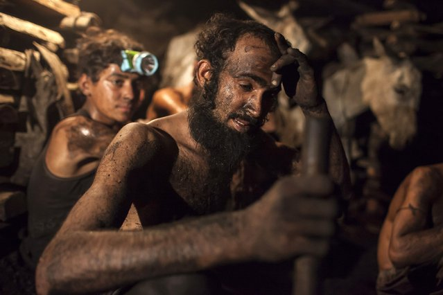 A miner wipes sweat from his forehead inside a coal mine in Choa Saidan Shah, Punjab province, April 29, 2014. (Photo by Sara Farid/Reuters)