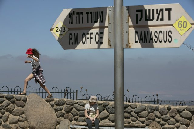 Israeli girls play near a sign at Mount Bental, an observation post in the Israeli-occupied Golan Heights that overlooks the Syrian side of the Qunietra crossing August 21, 2015. Israel said it killed four Palestinian militants in an air strike on the Syrian Golan Heights on Friday, after cross-border rocket fire from Syria prompted the heaviest Israeli bombardment since the start of Syria's four-year-old civil war. (Photo by Baz Ratner/Reuters)