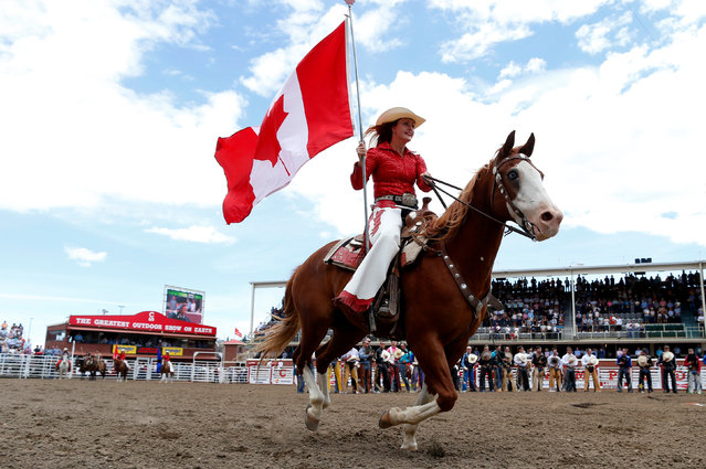 A Stampede ranch girl carries the Canadian flag during the national anthem at the Calgary Stampede rodeo in Calgary, Alberta, Canada July 8, 2016. (Photo by Todd Korol/Reuters)