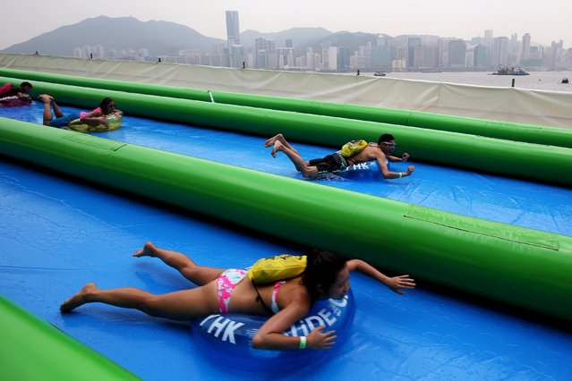 People slide down a 1,082 feet (330 metre) long inflatable water slide in Hong Kong, China August 22, 2015. (Photo by Tyrone Siu/Reuters)