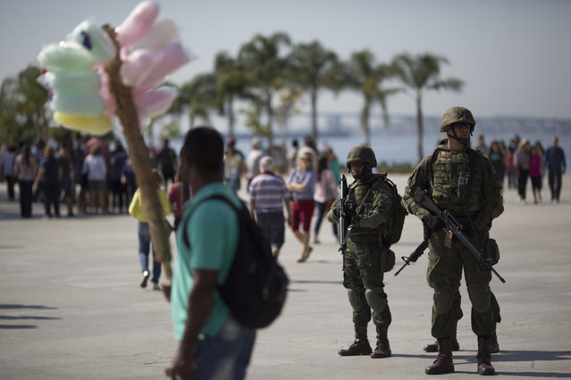 Soldiers stand guard in Maua square where a cotton candy vendor passes by in Rio de Janeiro, Brazil, Saturday, July 9, 2016, as security is deployed to get to know the areas they'll be patrolling during the Olympics. Roughly twice the security contingent at the London Olympics will be deployed during the August games in Rio, which are expected to draw thousands of foreigners to a city where armed muggings, stray bullets and turf wars between heavily armed drug gangs are routine. (Photo by Leo Correa/AP Photo)