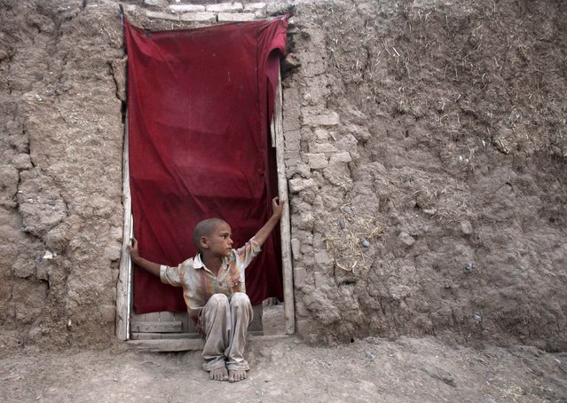 An Afghan refugee child sits at the front door of his home in the village of Sardaryab outside Peshawar August 6, 2014. (Photo by Fayaz Aziz/Reuters)