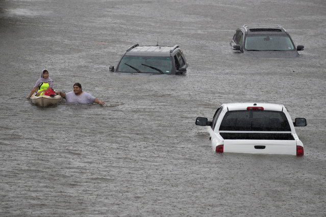 Jesus Rodriguez rescues Gloria Garcia after rain flooded Pearland, in the outskirts of Houston on August 27, 2017. (Photo by Adrees Latif/Reuters)