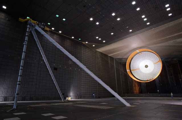 The parachute for NASA's Mars Science Laboratory passed flight-qualification testing in March and April 2009 inside the world's largest wind tunnel, at NASA Ames Research Center, Moffett Field, California. In this image, an engineer is dwarfed by the parachute, the largest ever built to fly on an extraterrestrial flight. It is designed to survive deployment at Mach 2.2 in the Martian atmosphere, where it will generate up to 65,000 pounds of drag force. The parachute has 80 suspension lines, measures more than 50 meters (165 feet) in length, and opens to a diameter of nearly 16 meters (51 feet). (Photo by NASA/Ames Research Center/JPL)