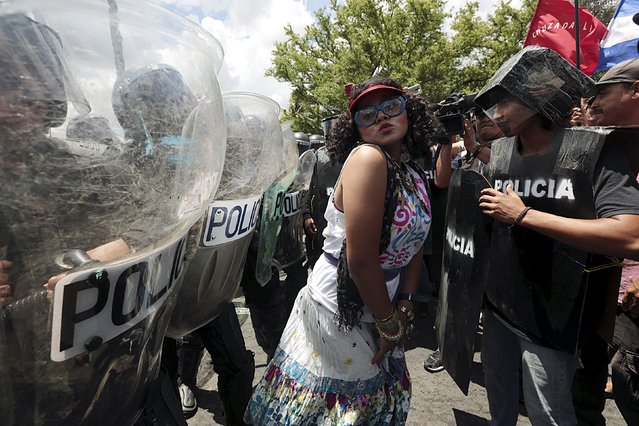 An opposition supporter dressed as Nicaraguan first lady Rosario Murillo performs in front of a line of riot police during a protest in front of the Supreme Electoral Council (CSE) building in Managua, Nicaragua August 26, 2015. The protesters said they were demonstrating to demand fairer elections in the country next year. (Photo by Oswaldo Rivas/Reuters)