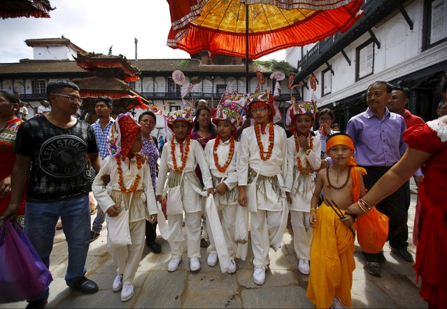 Boys dressed in white depicting holy cows participate in a parade to mark the Gaijatra Festival, also known as the festival of cows, in Kathmandu, Nepal August 30, 2015. (Photo by Navesh Chitrakar/Reuters)