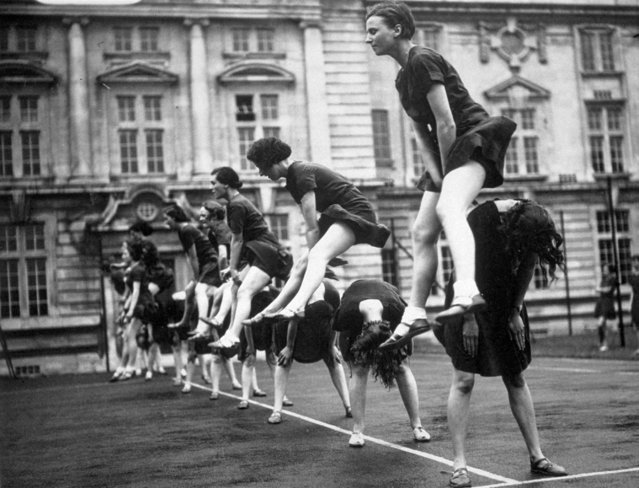 Students at University College Cardiff leap frogging during a physical training display. 17th May 1936.