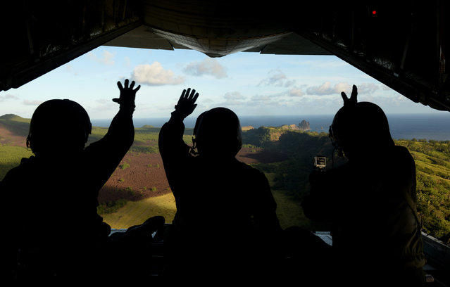 In this December 9, 2015 file photo provided by the U.S. Air Force, Japan Air Self-Defense Force airmen wave at residents of Pagan island in the Commonwealth of the Northern Mariana Islands after dropping a package to the islanders as part of Operation Christmas Drop. Community members and an environmental group on Wednesday, July 27, 2016, sued the U.S. Navy, the Department of Defense and the secretary of defense over a plan to turn two Pacific islands, including Pagan, into live-fire testing sites. (Photo by Staff Sgt. Benjamin Gonsier/U.S. Air Force via AP Photo)
