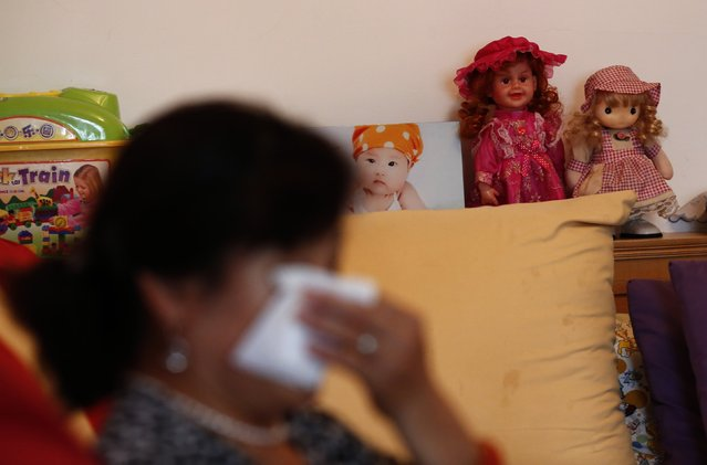 Hu, whose son Zhao's whole family was onboard Malaysia Airlines Flight MH370 which disappeared on March 8, 2014 wipes her tears during an interview with Reuters in Beijing July 24, 2014 as her granddaughter's framed picture is seen in the living room of her house. (Photo by Kim Kyung-Hoon/Reuters)