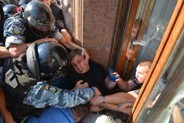 Riot police officers try to stop an opposition deputy as he tries to enter the building of Kiev city council through the window in Kiev on August 19, 2013. Several hundred of people rally at the Kiev city administration trying to break a city council session and demanding mayoral and city council elections. Opposition members complain about an  illegal session of the Kyiv City Council due to expiration of the deputies term in office. (Photo by Vitalii Lazebnyk/AFP Photo)