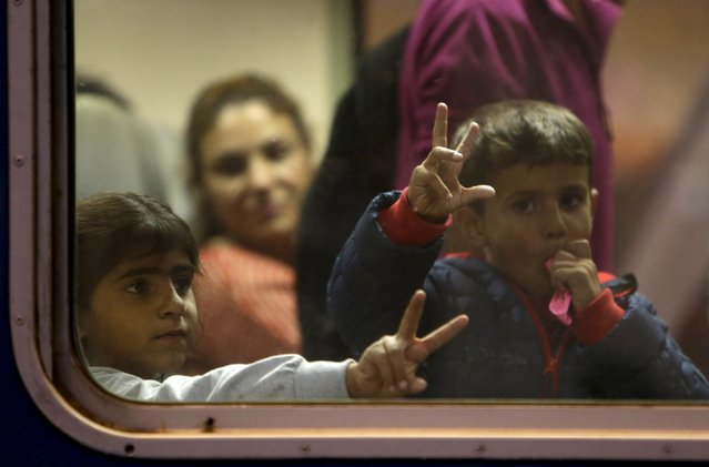 Migrant children look out through the window of a train at Keleti train station in Budapest, Hungary, September 5, 2015. (Photo by David W. Cerny/Reuters)