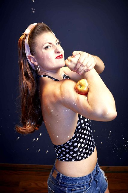 Mama Lou, aka Linsey Lindberg of the USA, used muscle power to squash eight apples in Los Angeles, California, on June 26, 2013. Once an accountant, she quit to be a performer and now blows up and pops hot water bottles and rips telephone directories in half. (Photo by Ryan Schude/Guinness World Records)