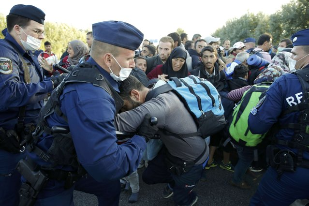 Hungarian police officers push back migrants at collection point in the village of Roszke, Hungary, September 7, 2015. Police used pepper spray on a crowd of migrants attempting to break through a cordon at Roszke, on Hungary's border with Serbia, on Monday, a Reuters witness said. (Photo by Marko Djurica/Reuters)