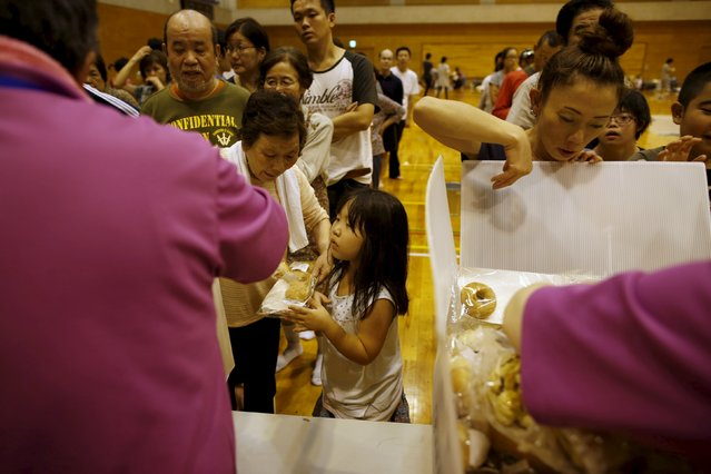 Evacuees from an area flooded by the Kinugawa river, caused by typhoon Etau, receive food supply at Ishige Sports Park acting as an evacuation center in Joso, Ibaraki prefecture, Japan, September 10, 2015. (Photo by Issei Kato/Reuters)