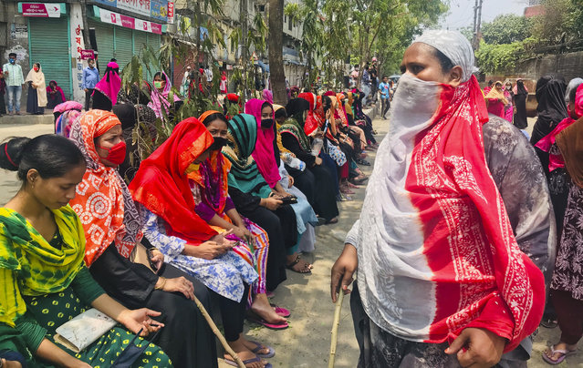 Bangladeshi garment workers block a road demanding their unpaid wages during a protest in Dhaka, Bangladesh, Thursday, April 16, 2020. Hundreds of Bangladeshi workers who produce garments for global brands protested in Dhaka and blocked a highway outside the capital on Thursday to demand unpaid wages during a nationwide lockdown that has forced most factories to suspend operations. (Photo by Al-emrun Garjon/AP Photo)