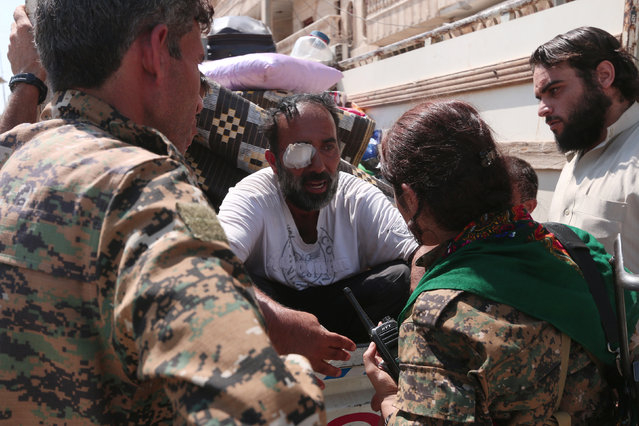Syria Democratic Forces fighters chat with an injured civilian who was evacuated with others by the SDF from an Islamic State-controlled neighbourhood of Manbij, in Aleppo Governorate, Syria, August 12, 2016. (Photo by Rodi Said/Reuters)