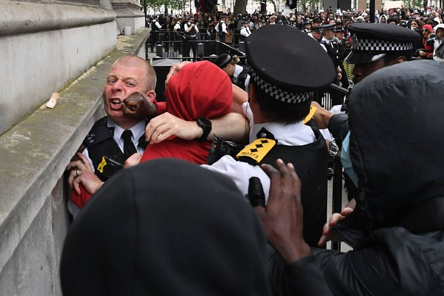 Police officers react as they attempt to detain a protestor near the entrance to Downing Street, during an anti-racism demonstration in London, on June 3, 2020, after George Floyd, an unarmed black man died after a police officer knelt on his neck during an arrest in Minneapolis, USA. Londoners defied coronavirus restrictions and rallied on Wednesday in solidarity with protests raging across the United States over the death of George Floyd, an unarmed black man who died during an arrest on May 25. (Photo by Daniel Leal-Olivas/AFP Photo)