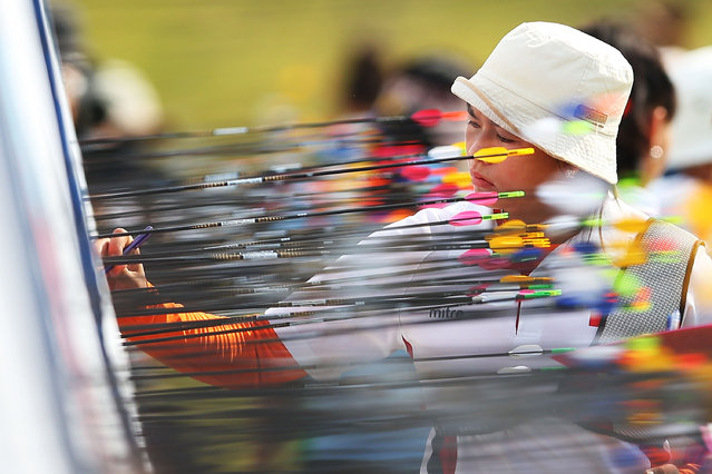 Athletes pull out arrows from their targets in Women's 70m Recurve Qualification Round during day four of the 2014 Asian Games at Gyeyang Asiad Archery Field on September 23, 2014 in Incheon, South Korea. (Photo by Brendon Thorne/Getty Images)